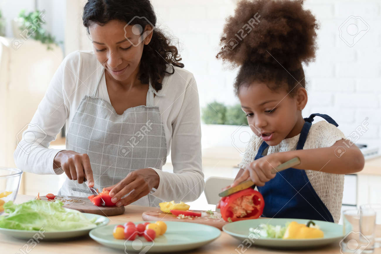 Happy mommy and cute daughter girl in aprons cooking together in kitchen. Mom and kid slicing fresh vegetables for salad, preparing healthy organic meal and talking. Family eating at home concept - 168073906