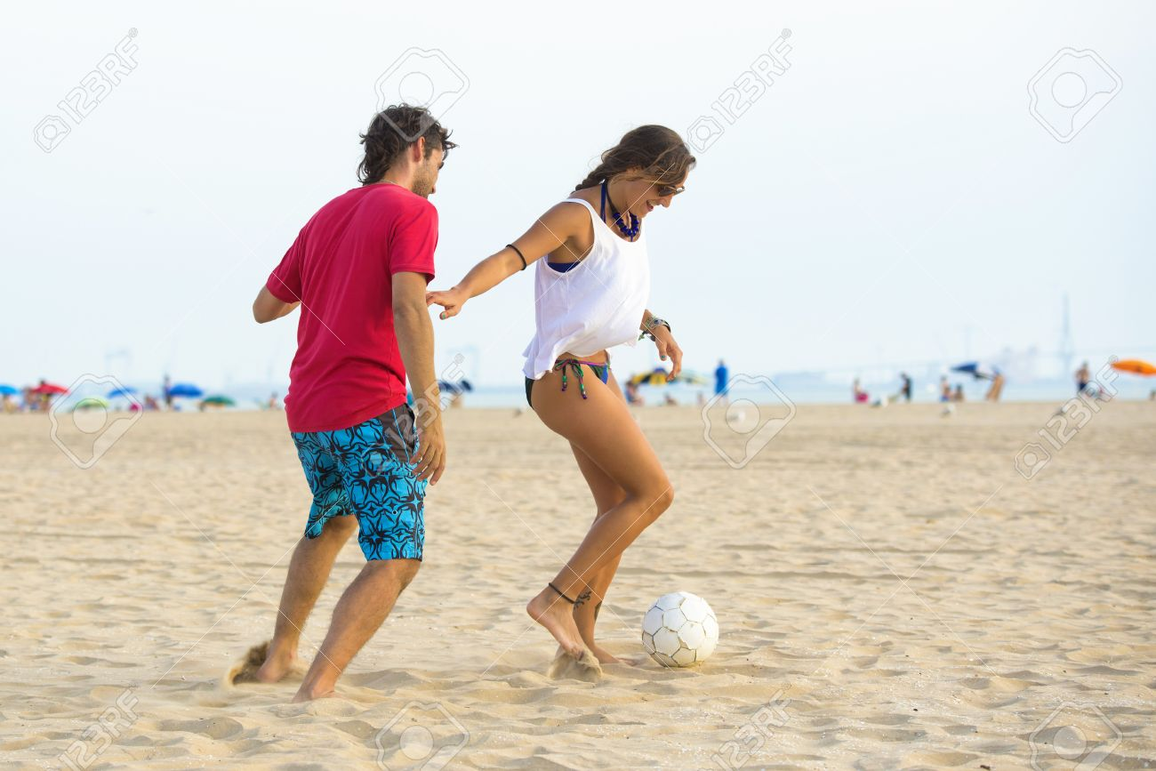 Joven Pareja Jugando Al Futbol En La Playa Al Atardecer Fotos