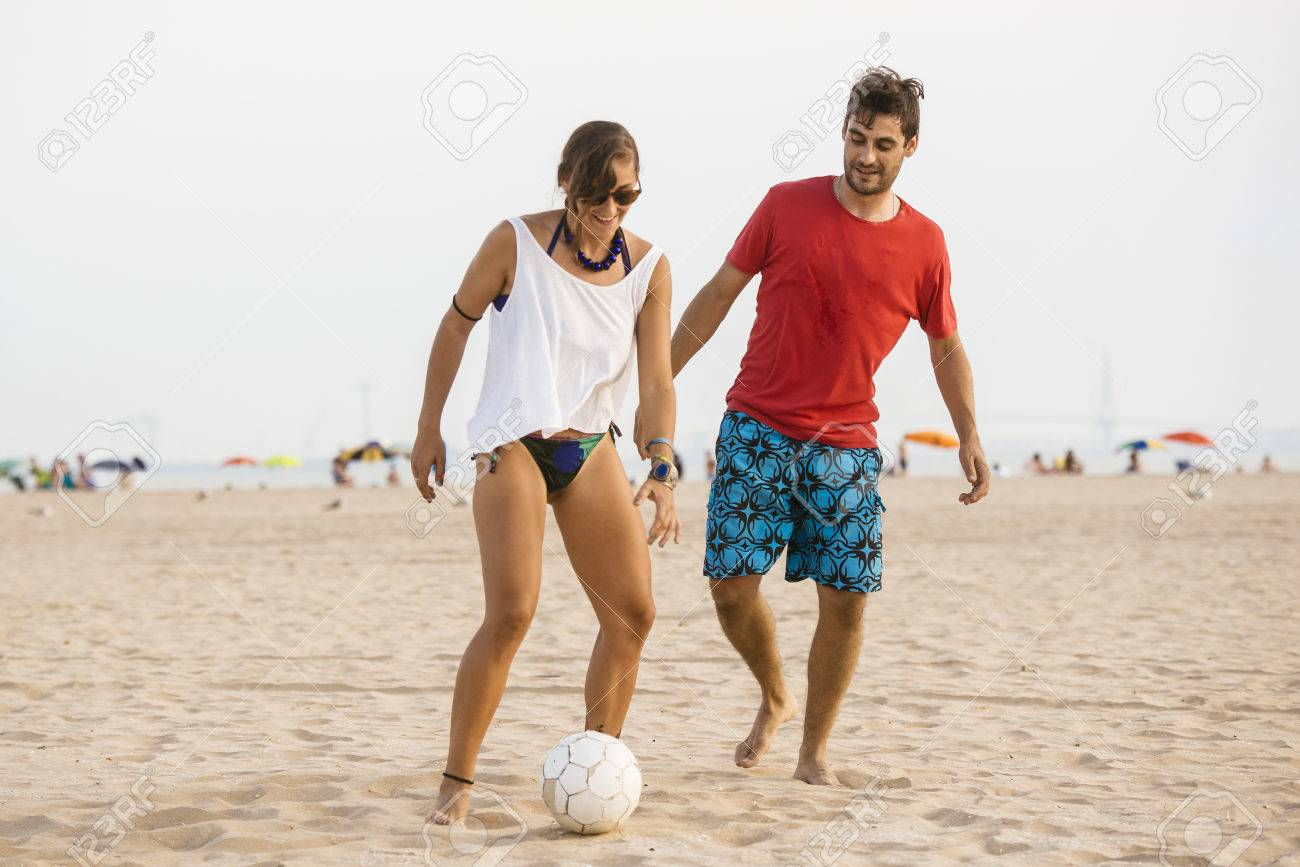 Joven Pareja De Jugar Al Futbol En La Playa Al Atardecer Fotos