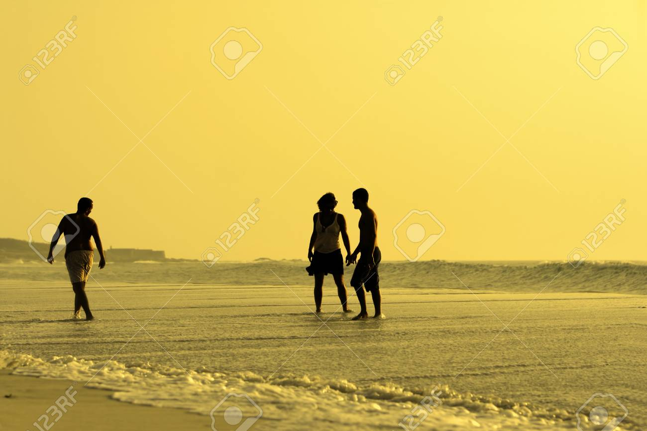 three silhouettes in a beach sunset Stock Photo - 1674808