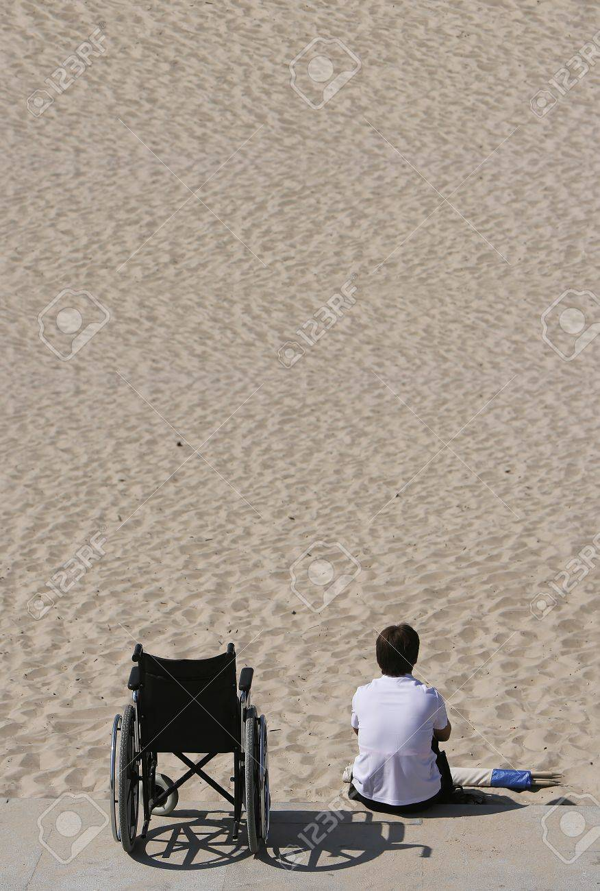 woman and wheel chair in the beach - 6988332