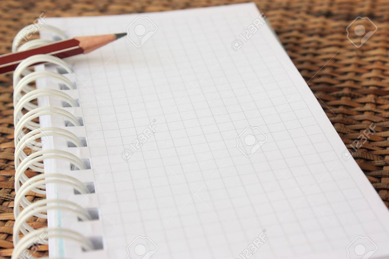 Spiral bound notebook with pencil over rattan desk- shallow dof Stock Photo - 6678786