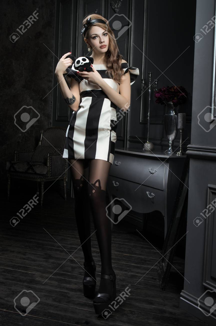 Sexy young woman in black and white dress standing in vintage dark room stock photo
