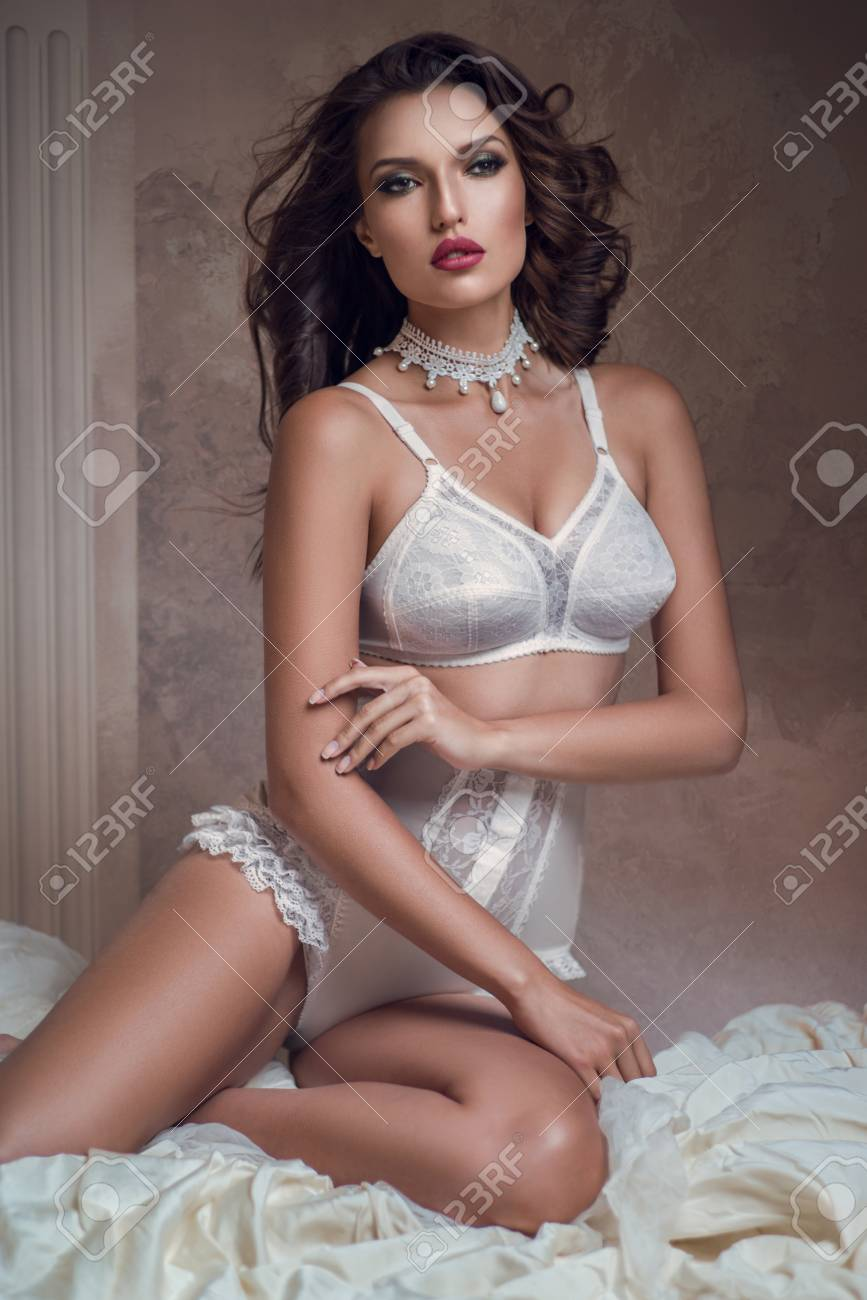 Beautiful woman in white lingerie sitting on bed and posing Stock Photo -  92036114 018b4c5ae