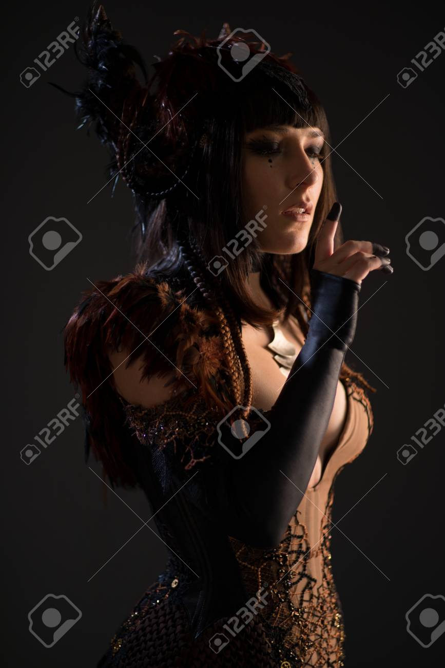 Portrait Of Brunette Woman In Gothic Gown Touching Lips And Looking ...