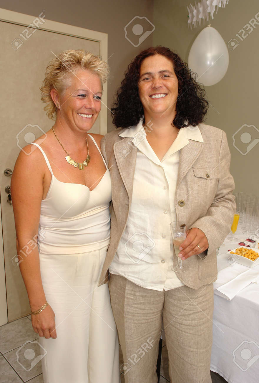 Lesbian mature couple posing and celebrating with Champaign at their wedding party after the official marriage ceremony. Same- marriage is fully legal in Belgium. - 504266