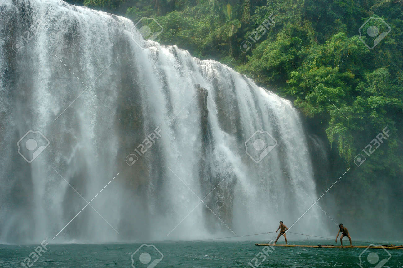 The wide cascading Tinuy-an waterfalls near Bislig city, Mindanao, Philippines, called the Niagara of the Philippines, in a pristine virgin rain-forest setting. Two boys playing on a raft in front. - 954432