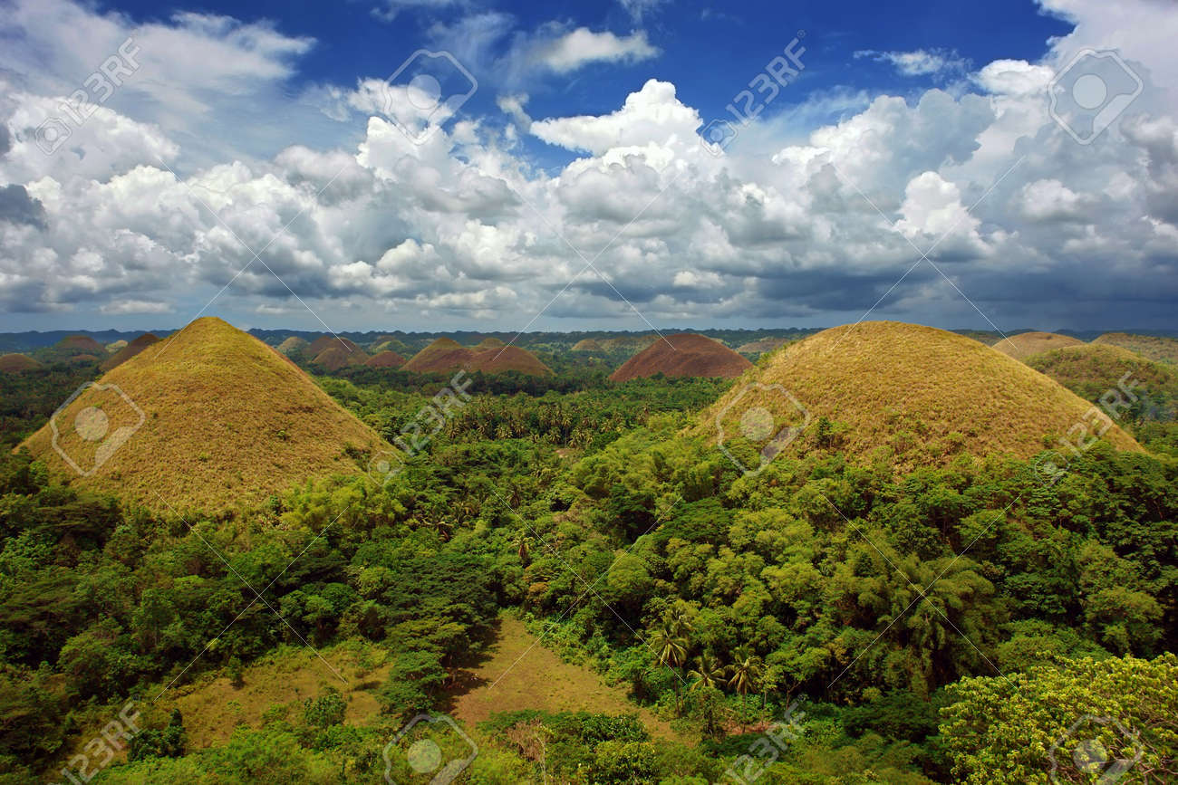 A panorama of the famous Bohol Chocolate Hills, a very prominent tourism landmark in the Philippines, colorful and under a majestic cloudscape. Stock Photo - 1437763