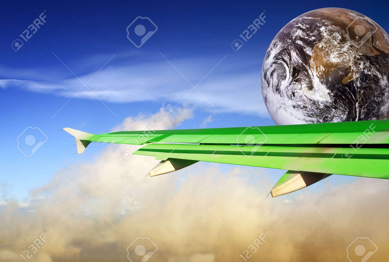 Globe with green airplane wing flying over a tropical cloudscape. Metaphor or concept of energy conservation and more efficient flying in the aviation industry to save energy and reduce CO2 output in order to combat global warming. - 2326655