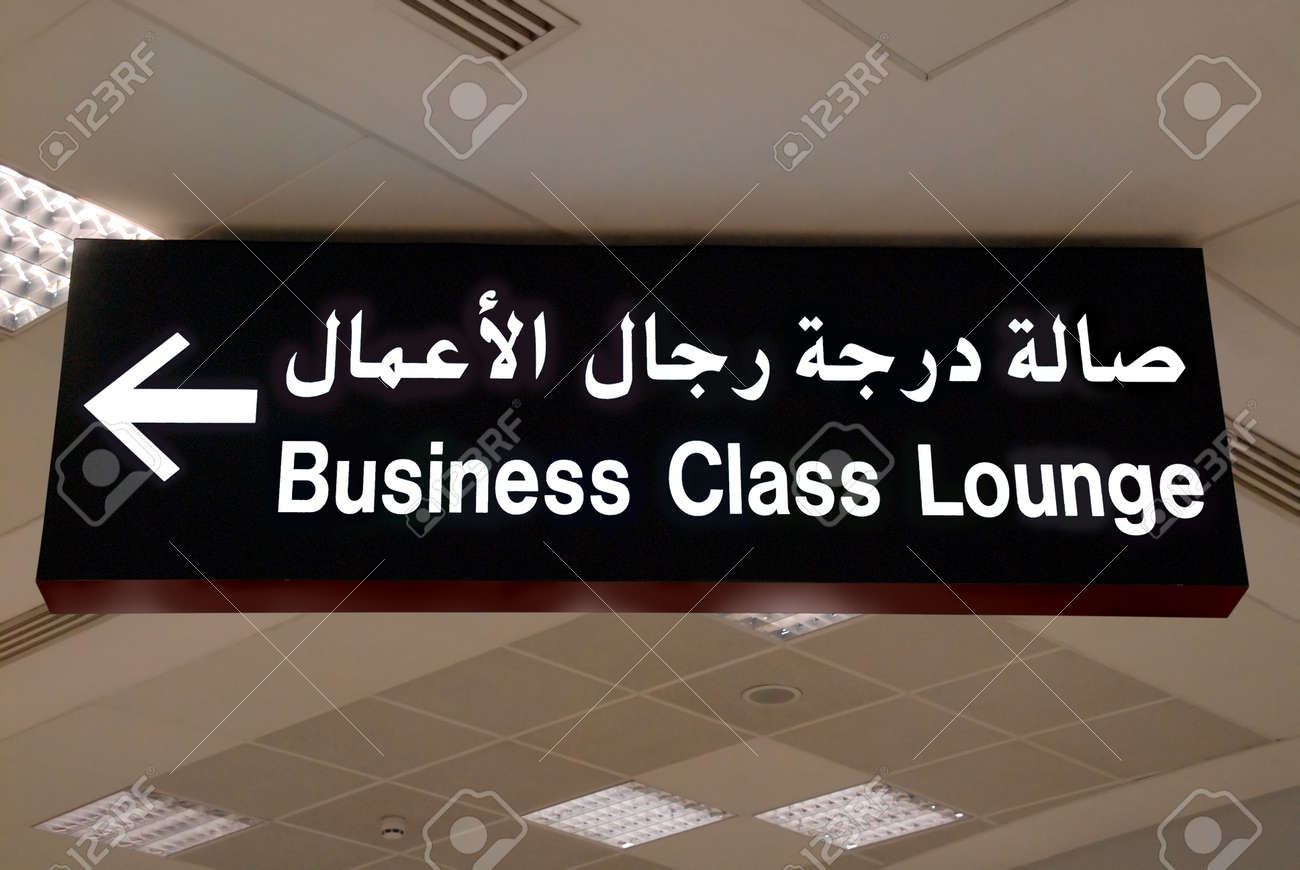 Ceiling sign in Arabic and English in an Arab airport: direction to the business class lounge (Doha, Qatar, code DOH). - 2511749