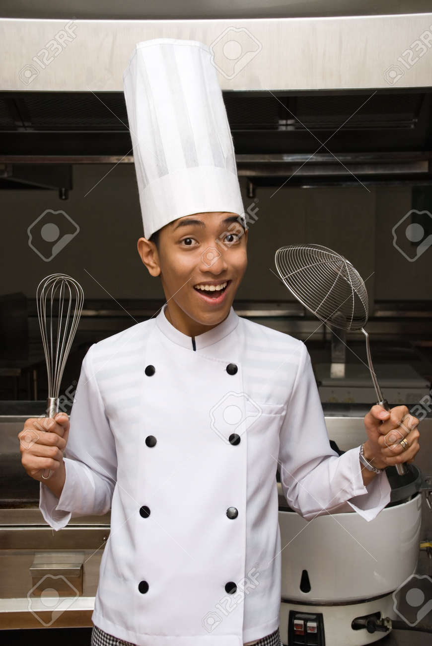 Young male smiling Chinese cook or chef proudly showing kitchen utensils in the kitchen of  a large hotel restaurant. Stock Photo - 4124054