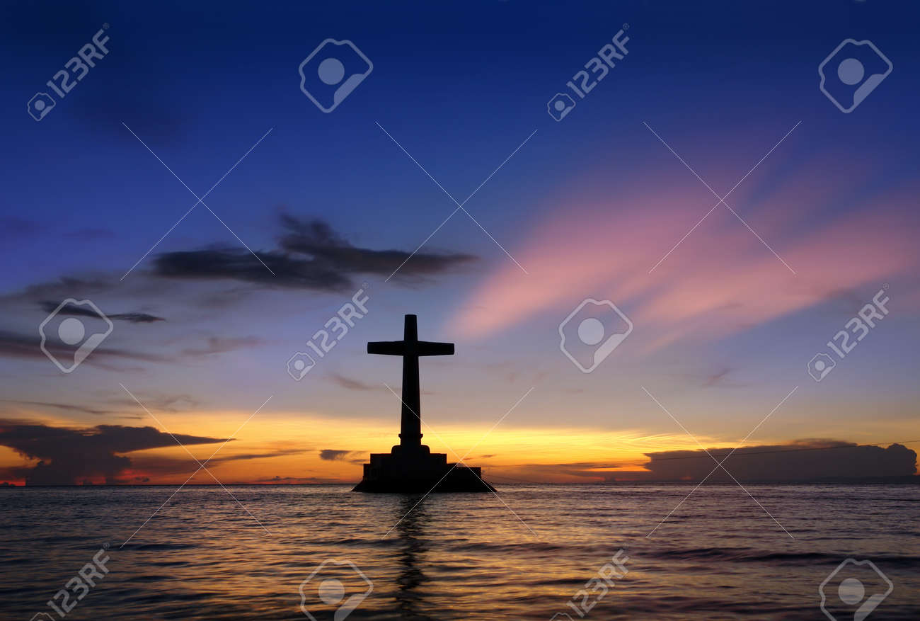 Colorful tropical marine sunset with a large concrete cross silhouette over Sunken Cemetery, Camiguin, Philippines. - 4326508