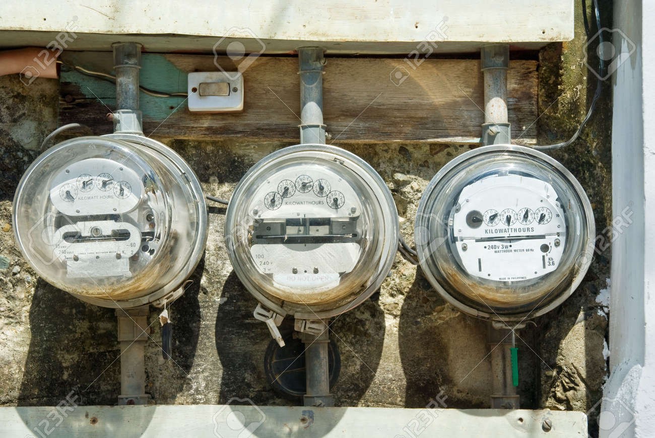 Three rusted old mechanical residential electricity meters in a row mounted on a poor wall outdoors with messed tubes and wiring. - 5196063