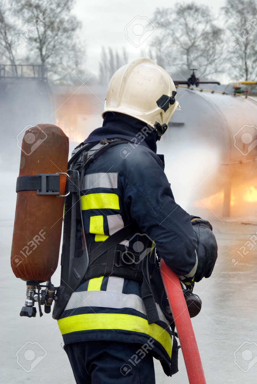Firefighter in protective clothing, with helmet and oxygen tank extinguishing tank fire with a hose and water jet in an industrial location. Back view. - 5492128