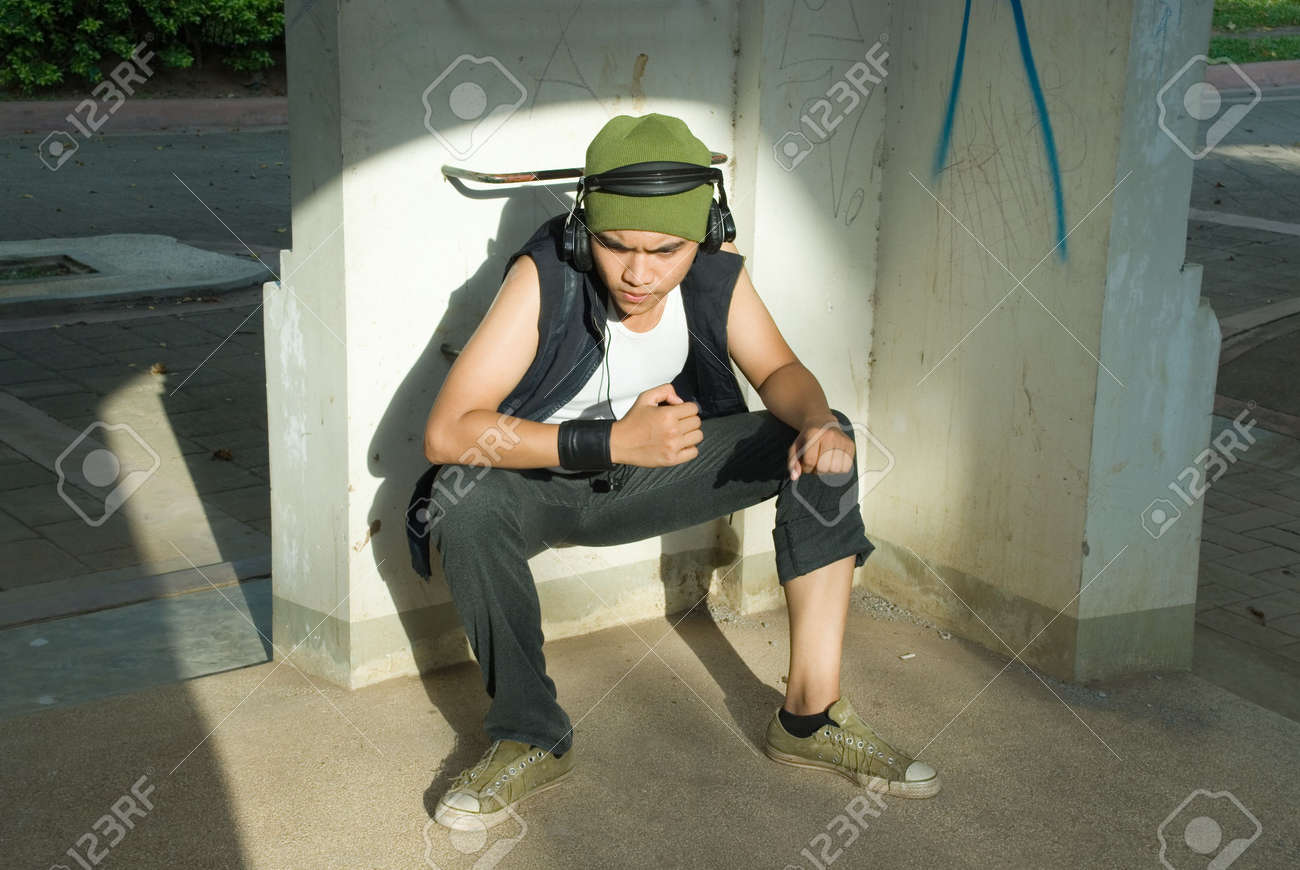Young Hispanic male rapper with cap and headphones sitting in a sunny spotlight, in a wasted urban environment vandalized with graffiti. - 5526232