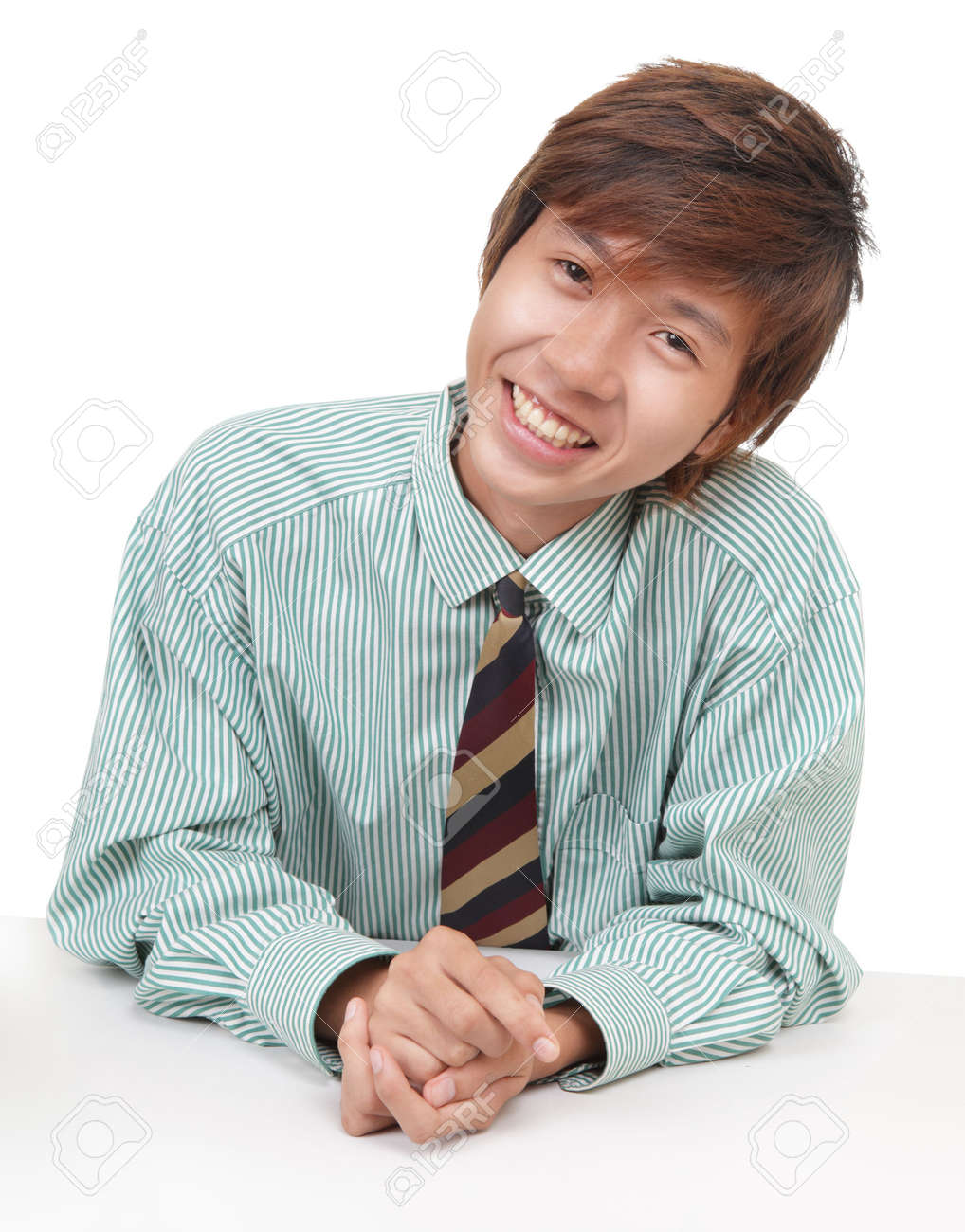 Friendly smiling young Asian or Korean businessman, salesman or consultant, sitting at his desk and leaning over like convincing a customer. Isolated over white. - 6186285