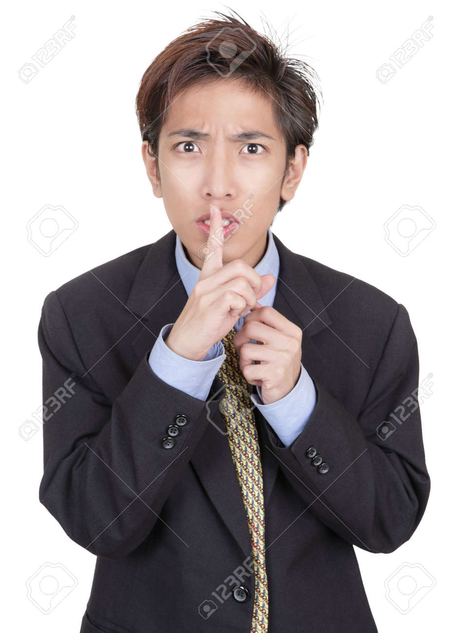 Young Chinese businessman hushing with fingers on lips and a mesmerizing urging gaze insisting on discretion and secrecy. Isolated over white. Stock Photo - 6338890