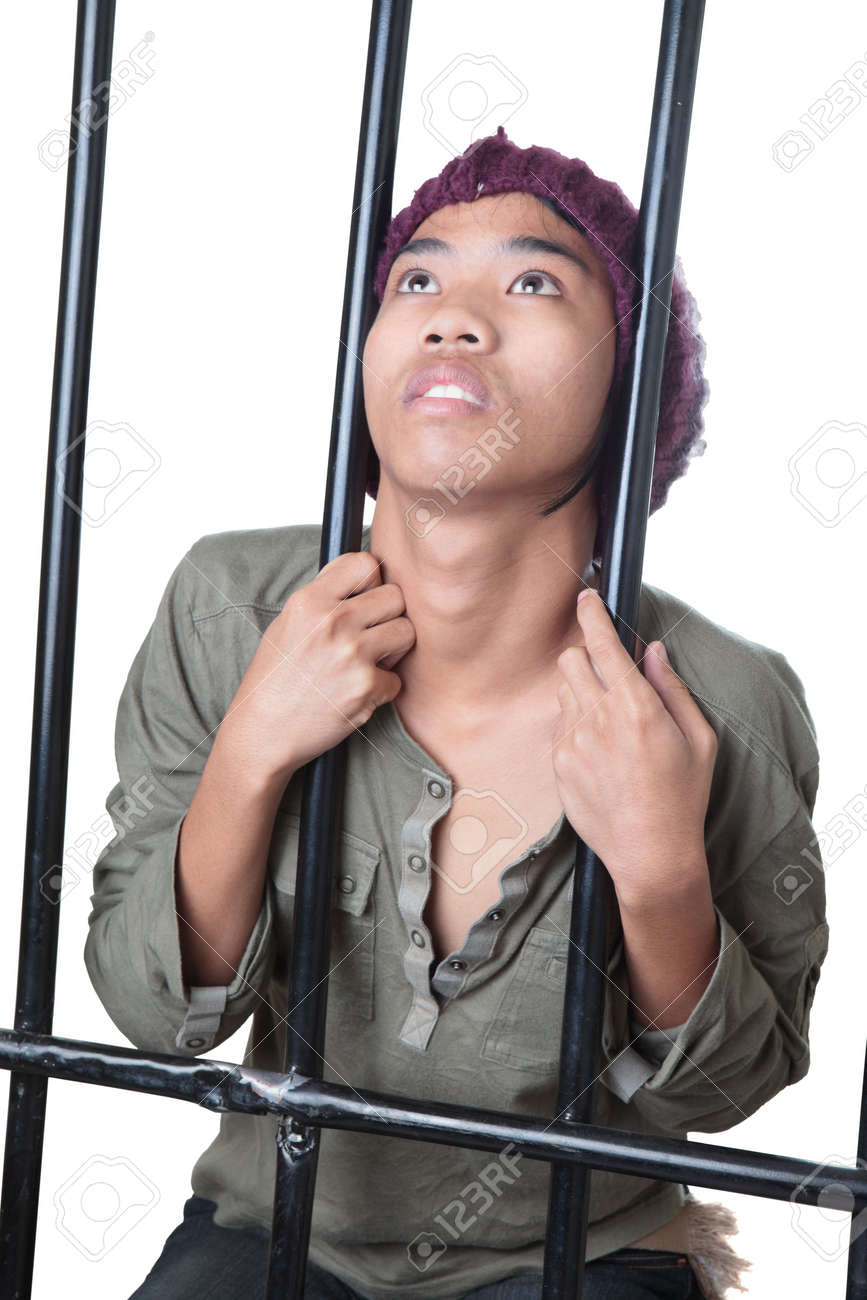 Asian male teenager with cap and grunge shirt holding and standing behind prison bars, looking up desperately and gasping. Isolated over white. Stock Photo - 6483178