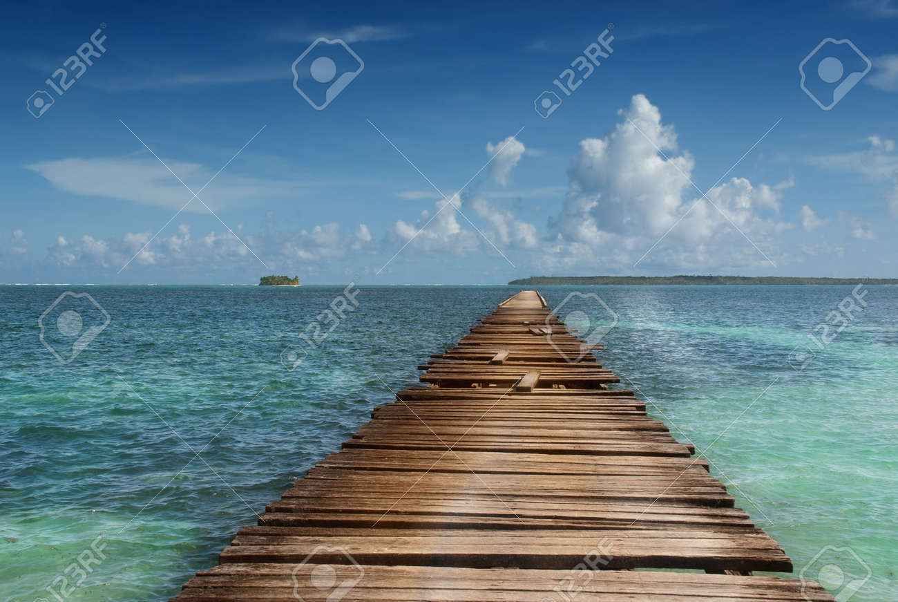Wooden pier pointing to pristine island in tropical sea. Concept of simplicity, purpose, direction and infinity. - 8701319