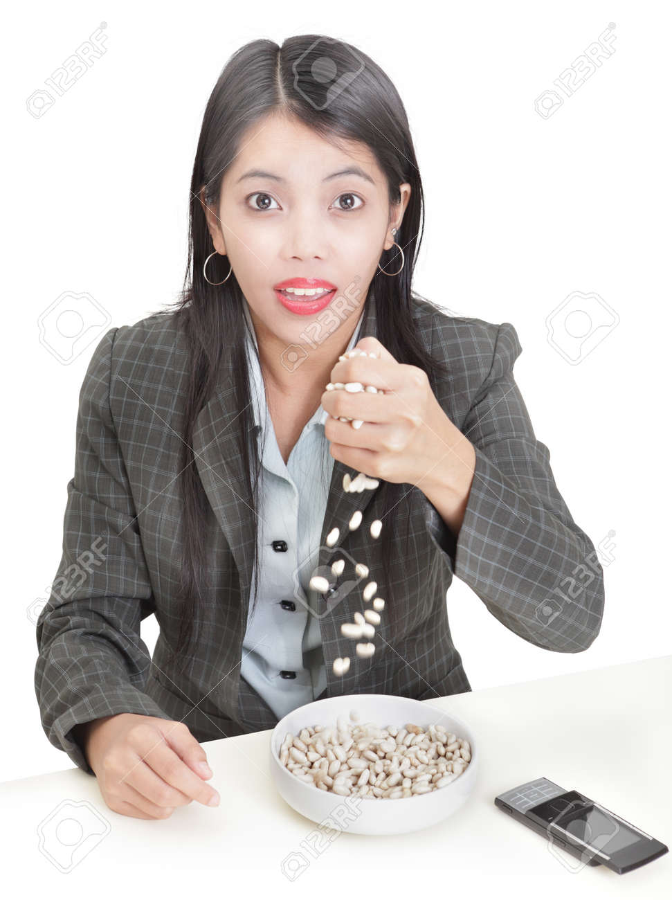 Young Asian businesswoman at her desk spilling the beans: English idiom and metaphor of betraying a secret or bring out confidential information. Isolated over white. Stock Photo - 9229788