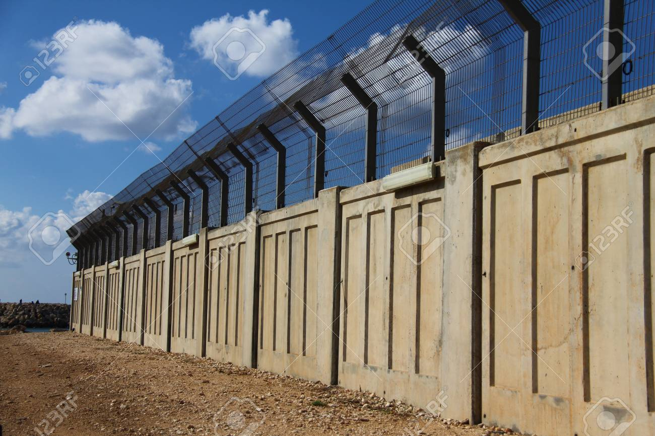 A secured industrial zone with concrete fence on the blue sky background Stock Photo - 16585389