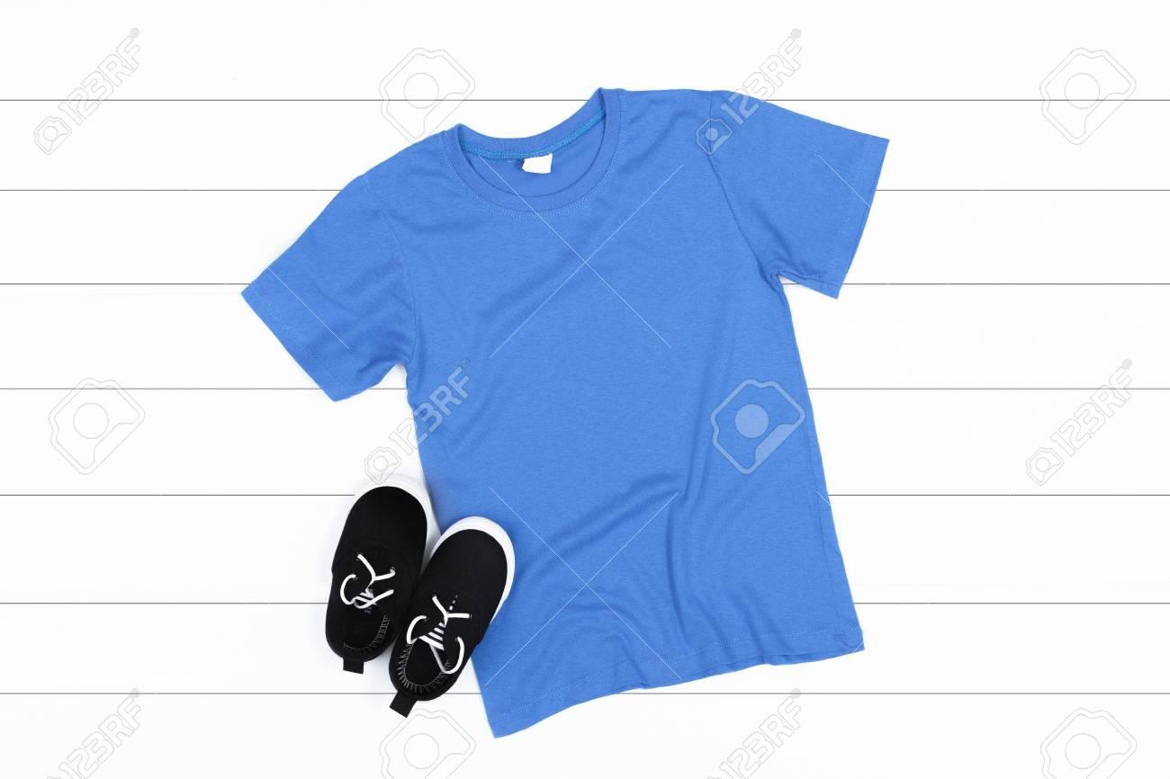 Blue Kids T Shirt Mockup On A White Wooden Background Flat