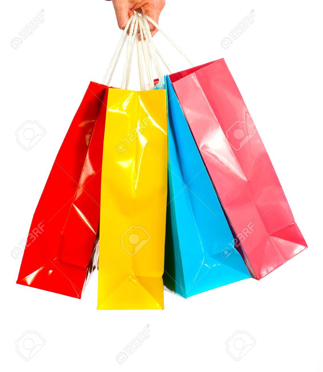 56bd05eca9 Foto de archivo - Una mano agarra señoras varios colores brillantes bolsas  de la compra en un fondo blanco