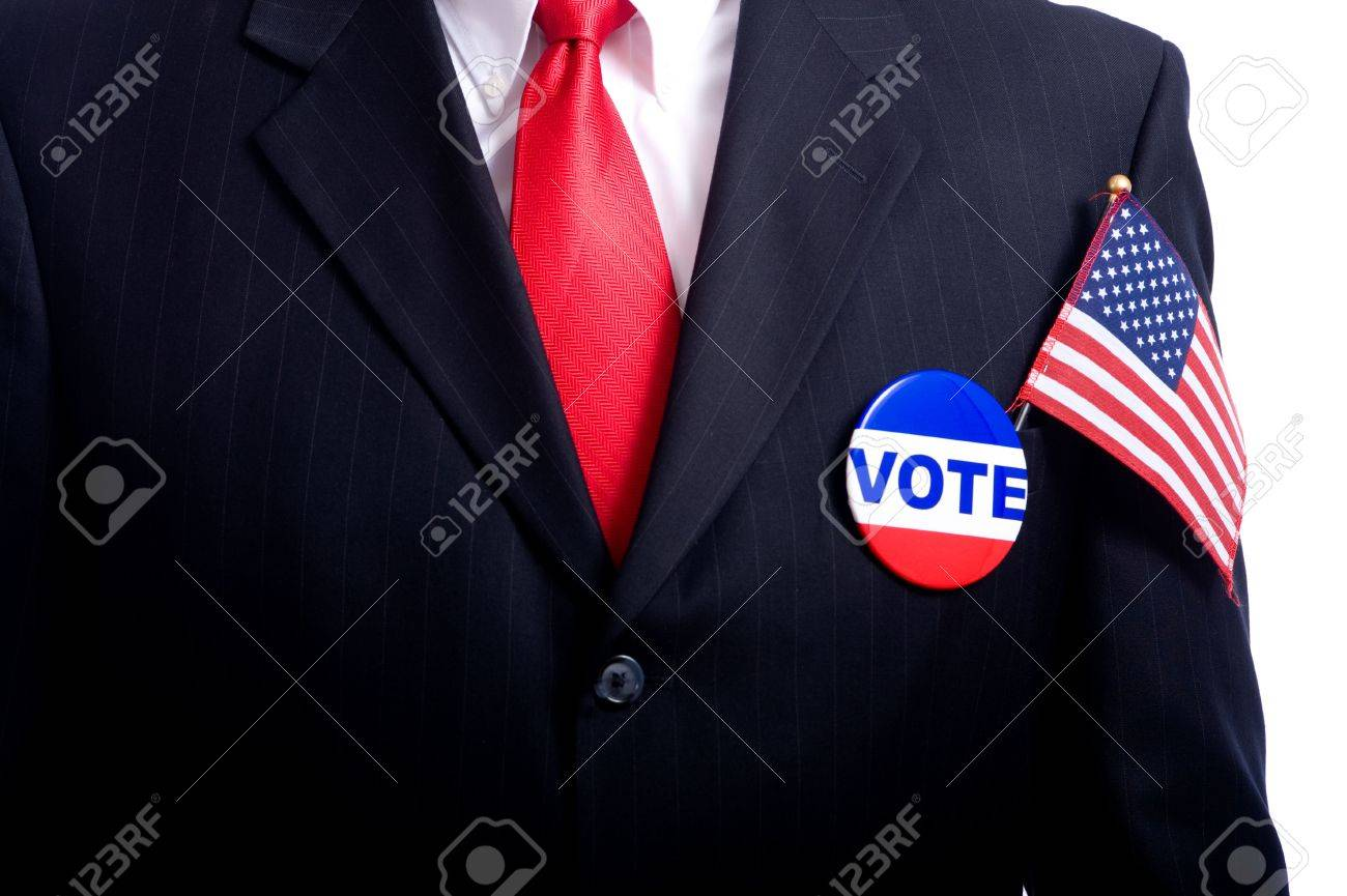 A man wearing a blue business suit and tie with a vote button and US flag.  Election day background or concept Stock Photo - 4722829