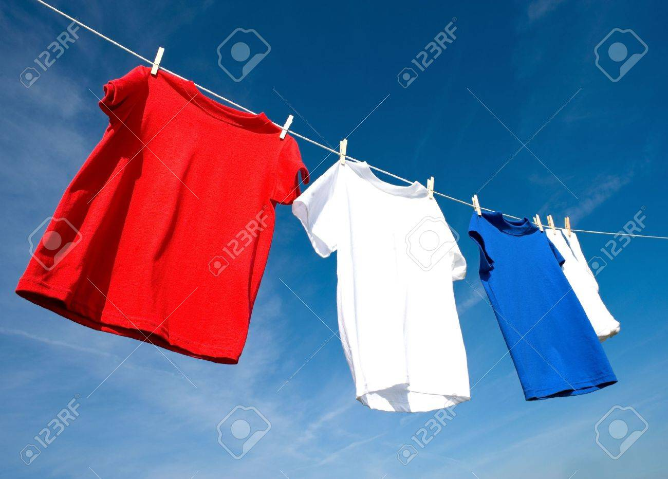a set of red, white and blue T-shirts hanging on a clothesline on a beautiful, sunny day, add text or graphic to shirts or copy space.  Independance day or USA theme. Stock Photo - 4725789