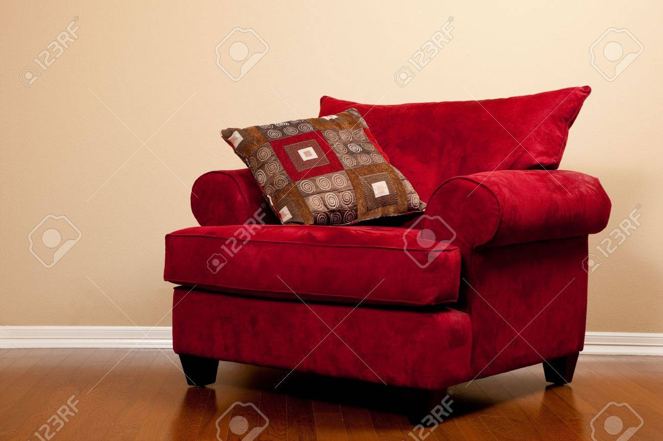 a modern red fabric oversized chair on hardwood flooring in a house with copy space stock