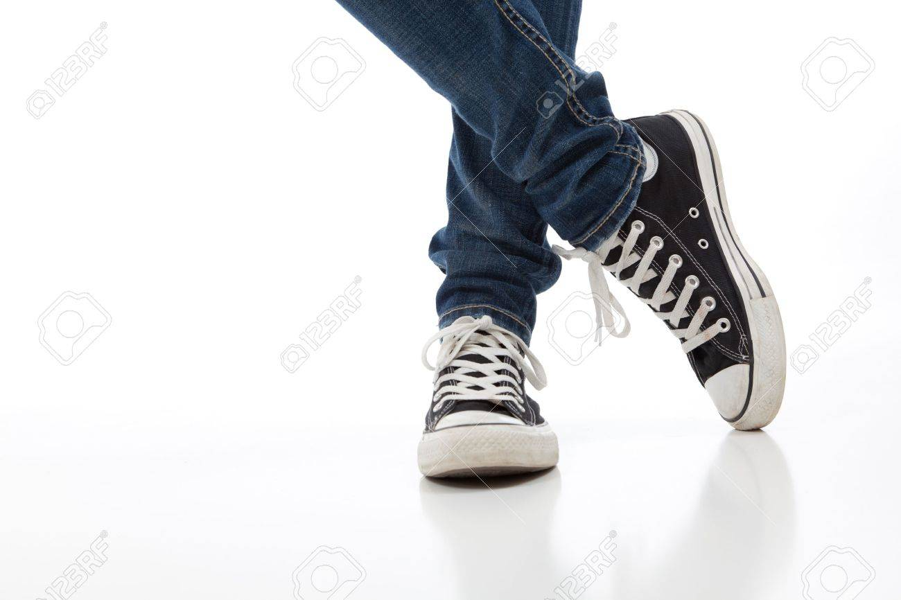 Person Wearing Vintage Tennis Shoes On A White Background With