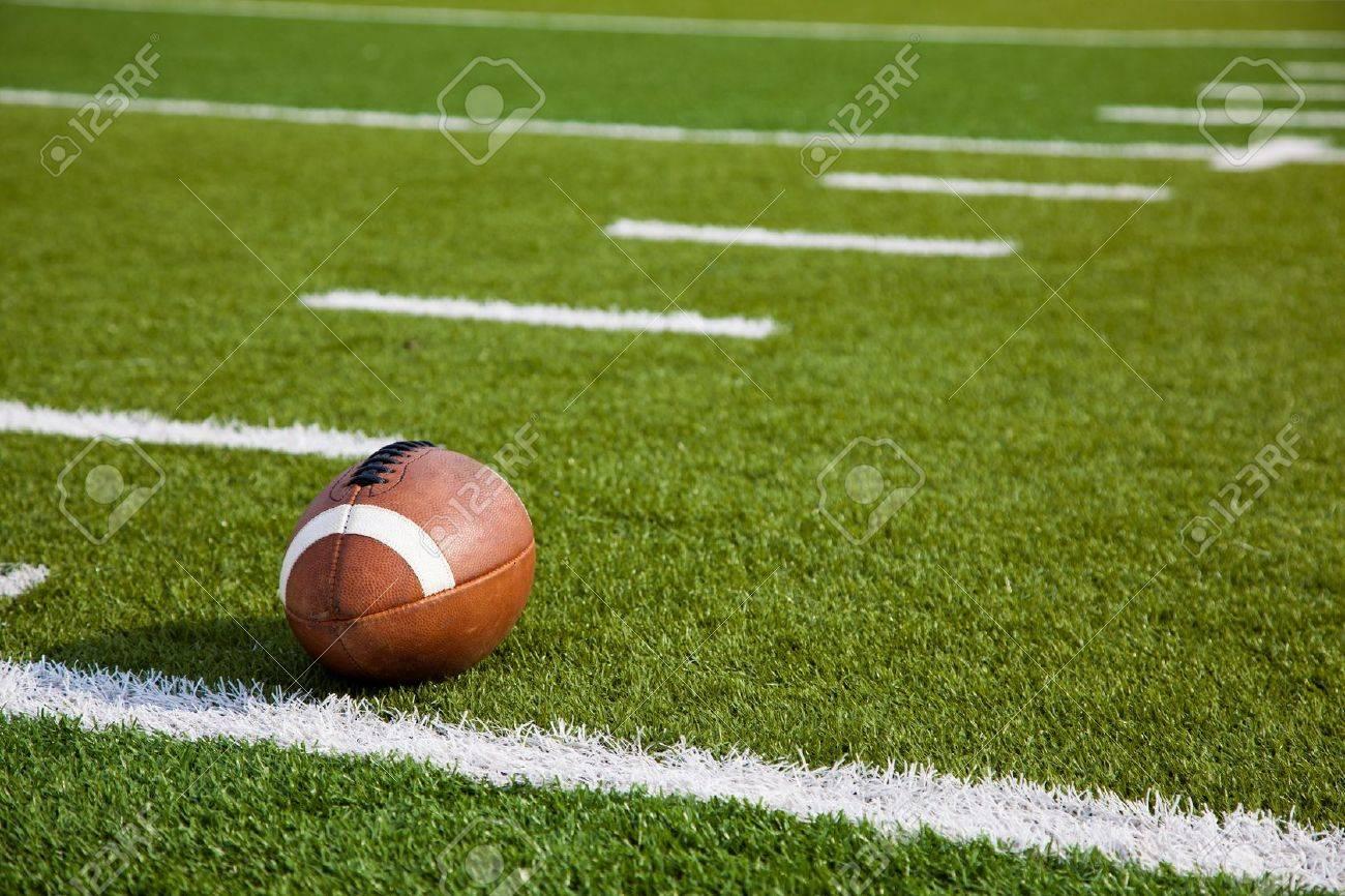 A American football on a green football field - 20654926