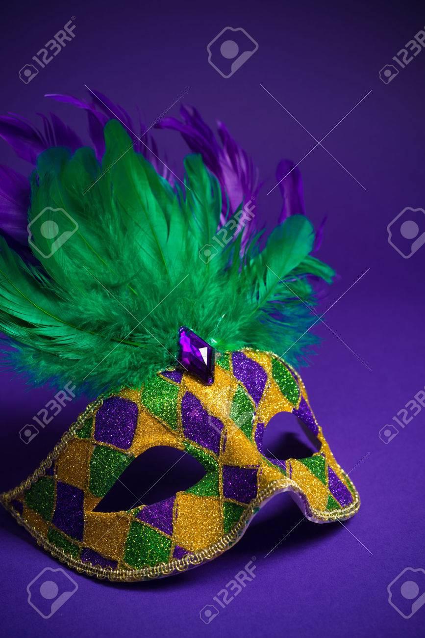 Festive mardi gras, venetian or carnivale mask on a purple background - 25892102