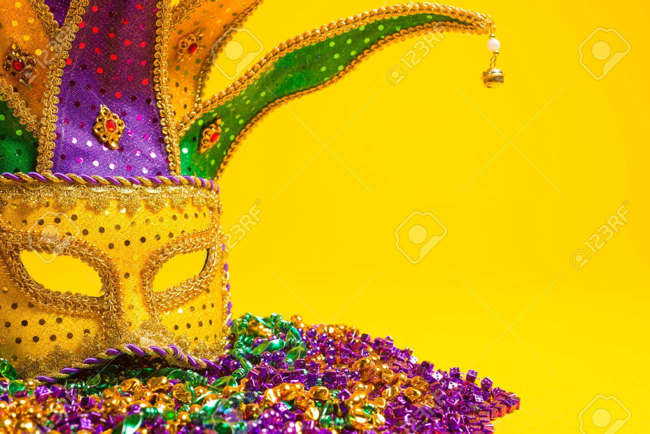 A festive, colorful group of mardi gras or carnivale masks on a yellow background Venetian masks - 25892128