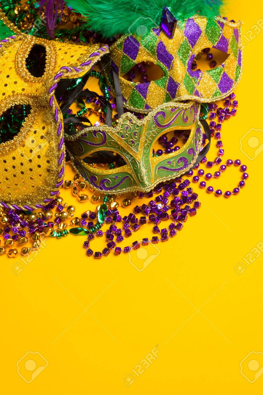 A festive, colorful group of mardi gras or carnivale masks on a yellow background Venetian masks - 25892134