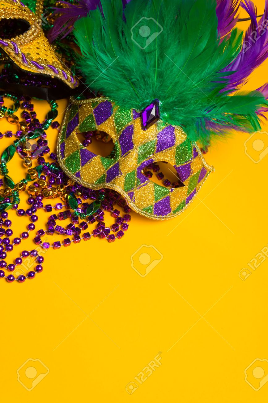 A festive, colorful mardi gras or carnivale mask on a yellow background   Venetian masks Stock Photo - 25892136