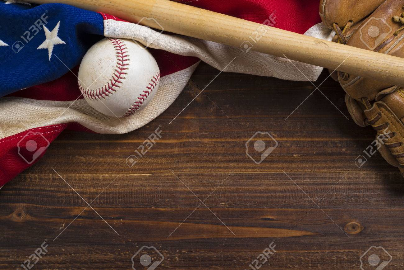 An old, antique American flag with vintage baseball equipment on a wooden bench - 44662597