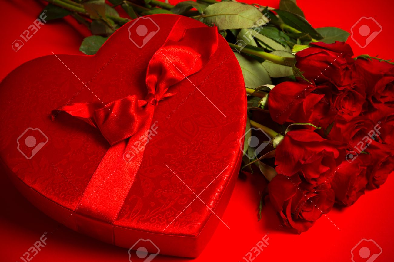 Long stem red roses and box of candy on a red background long stem red roses and box of candy on a red background valentines day gift buycottarizona