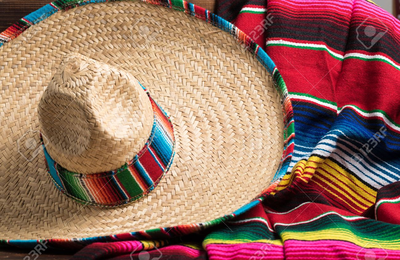 A traditional Mexican Sombrero and serape blanket on a yellow background with copy space - 44715876