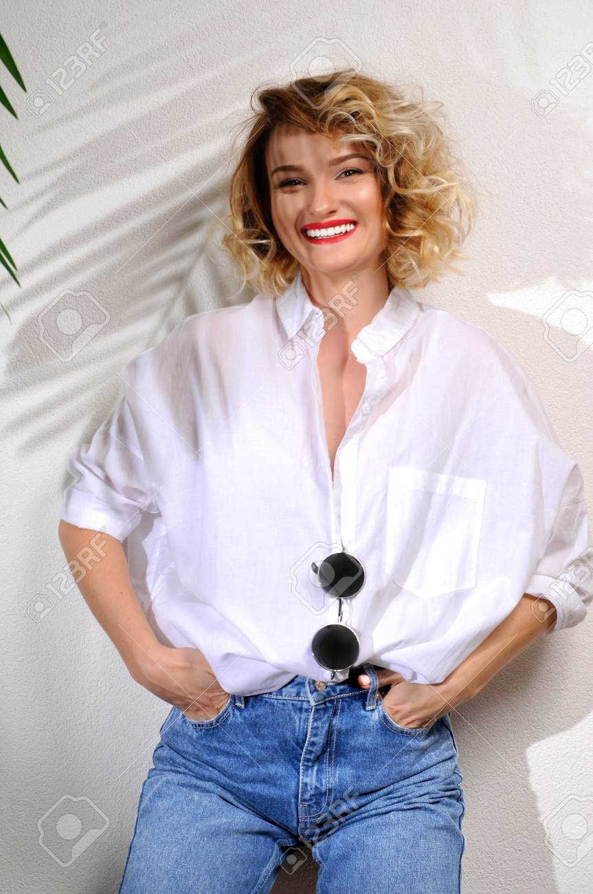 Fashion smiling blond woman in jeans and white shirt with sunglasses on white wall with shadow of palm leaves