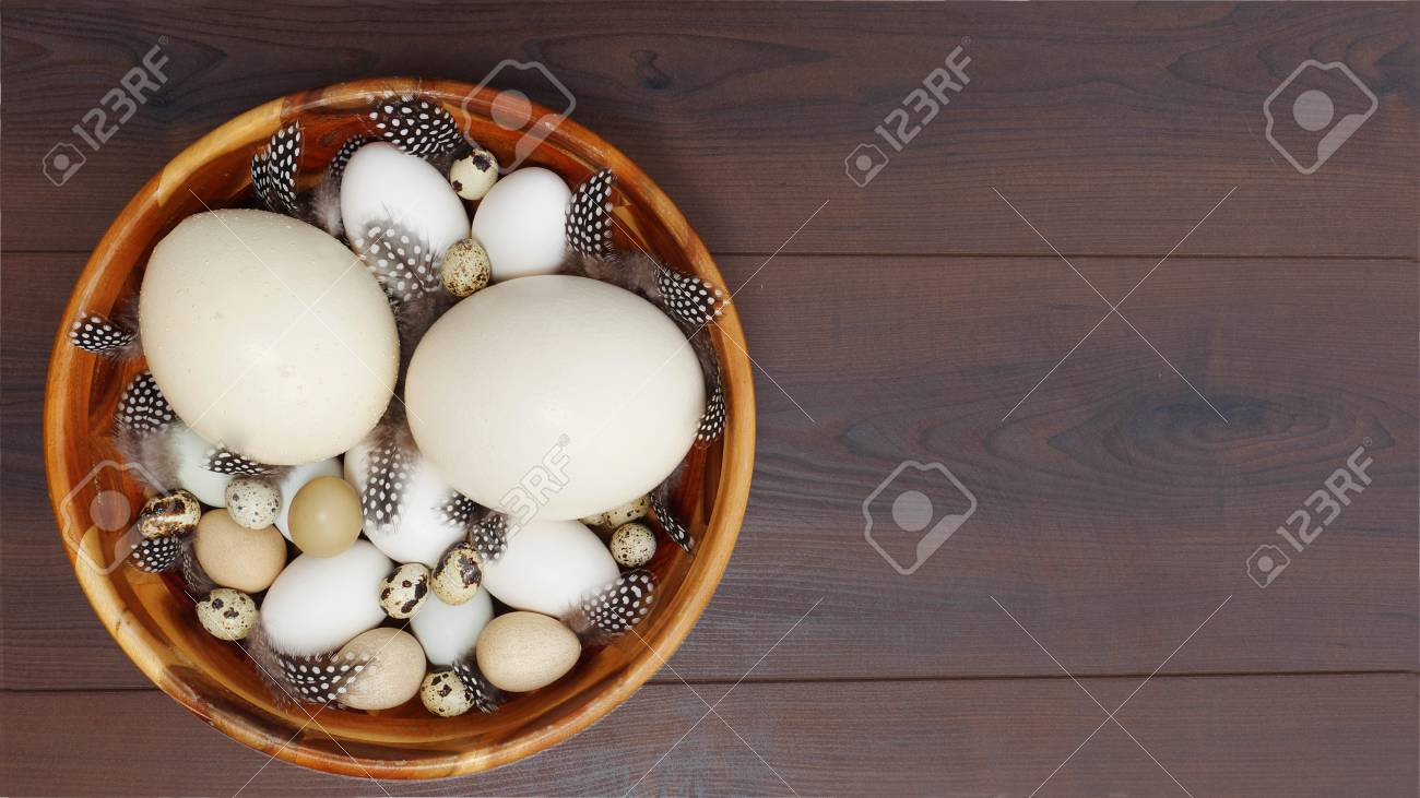 Different Blown Eggs Arranged In A Wooden Bowl And Decorated