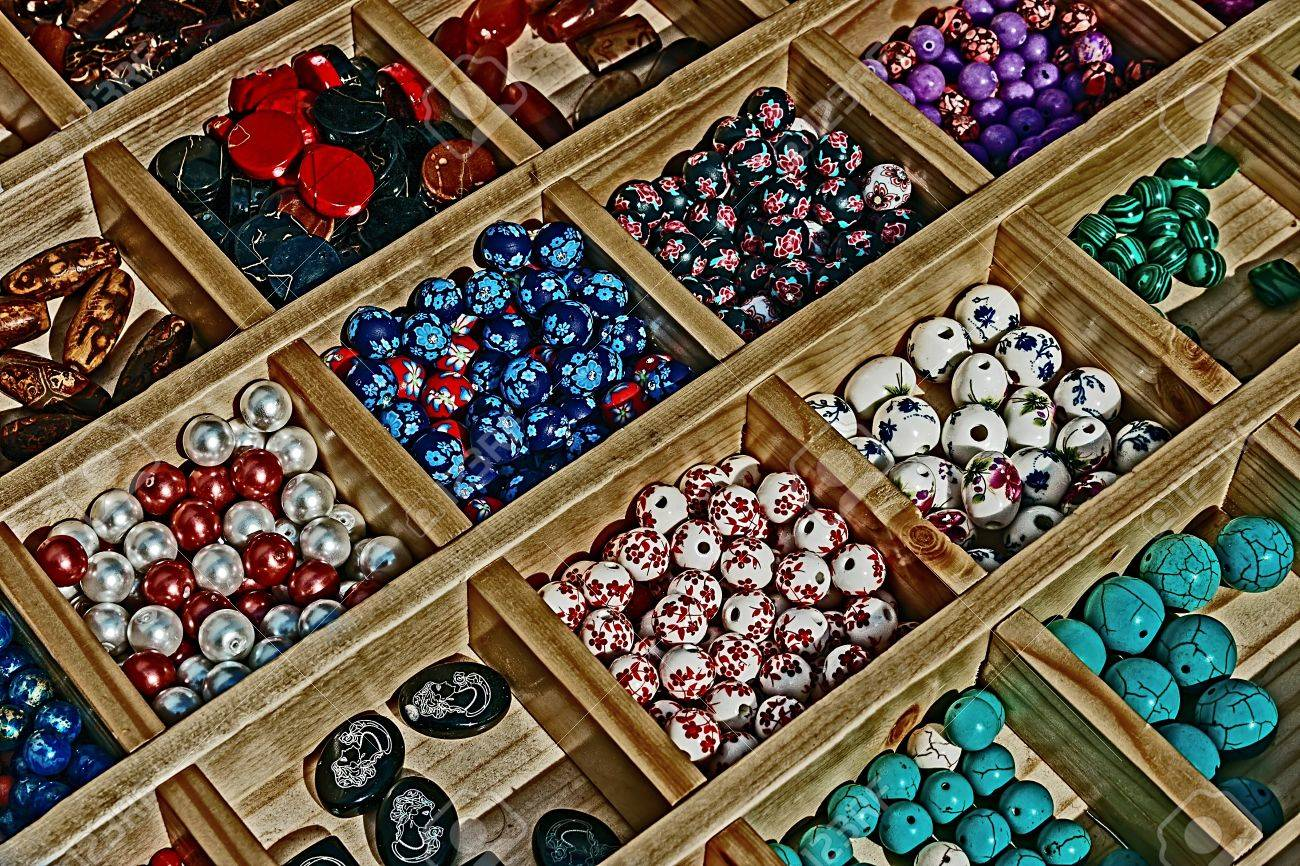 Colored beads with different shapes, presented in a wooden box divided - 17543966