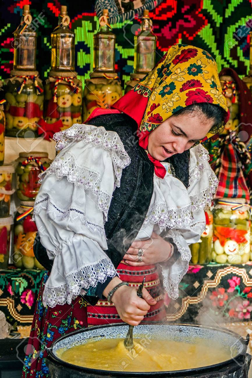 Young woman dressed in traditional costume from Maramures, Romania, mixed polenta in a large pot on a background with traditional embroidery.Street winter Fair in Timisoara, Romania, December 2014. - 36749781