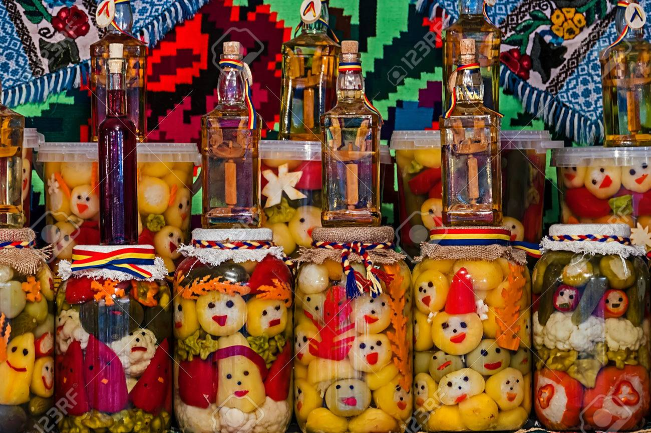 Jars with pickles and bottles with alcohol, traditional from area Maramures, Romania, displayed on a background with traditional embroidery. - 37435143