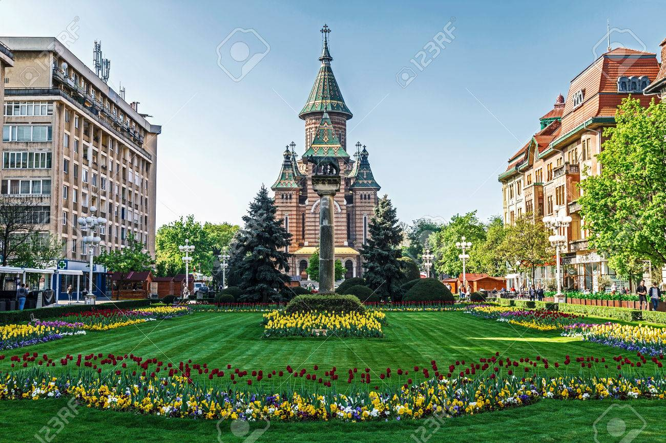TIMISOARA, ROMANIA - APRIL 15, 2016: Floral arrangements in Victory Square, with orthodox cathedral in background. - 57927749