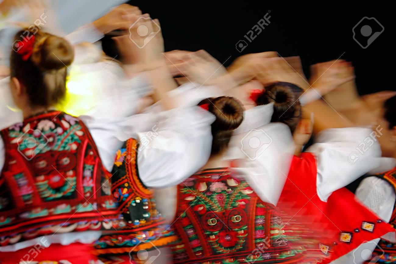 Abstract blur moving with amazing dance. Young Romanian dancers in traditional costume. - 61942122