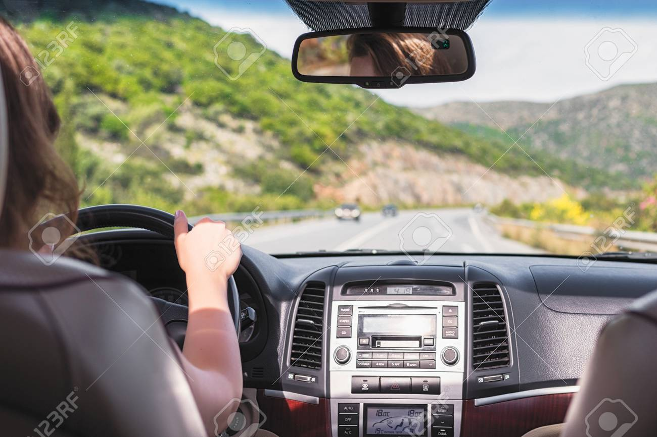 The girl is driving on the road on Tenerife, Canary Islands. View from the back seat of the car on the windshield, road and the driver - 122592729