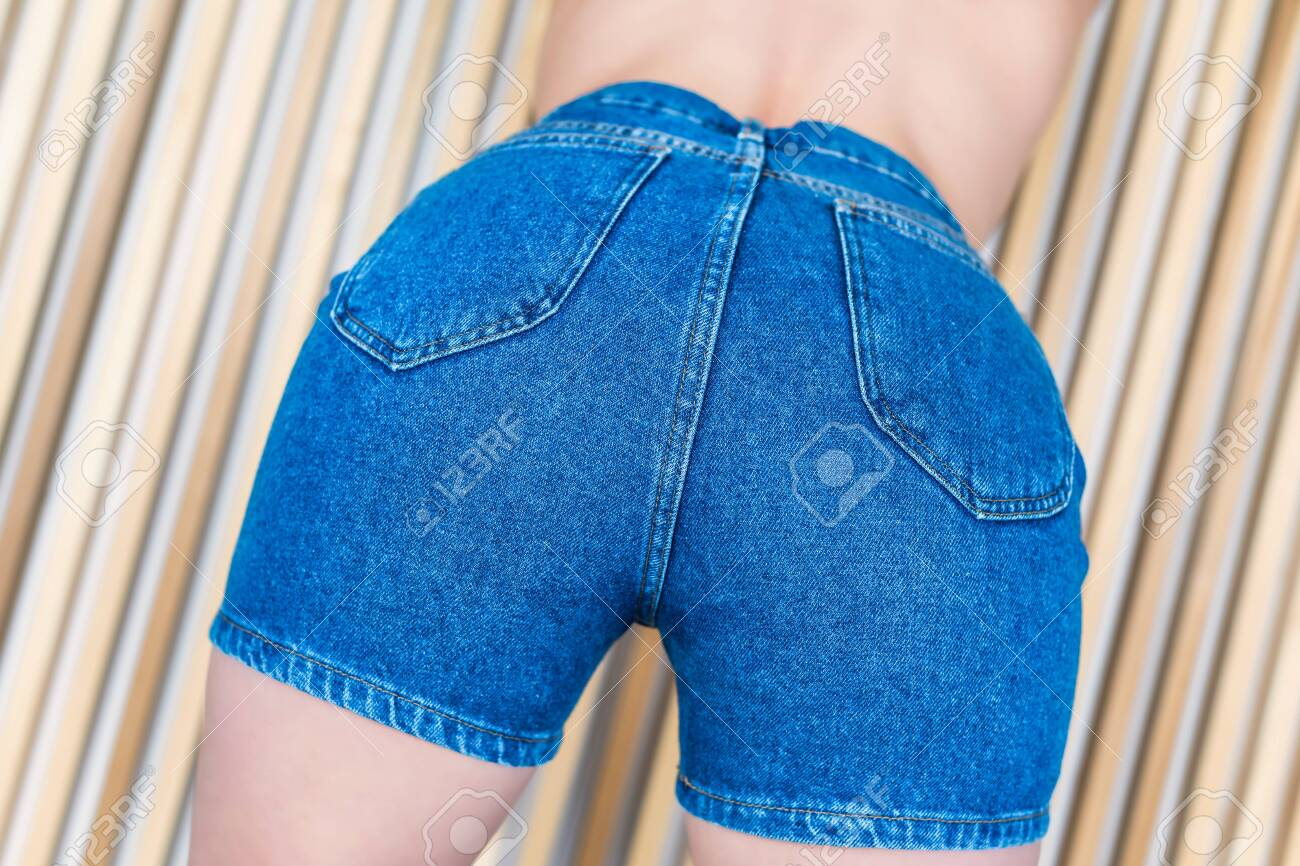 Bottom view on women's in denim shorts on the background of wooden beams - 124871661