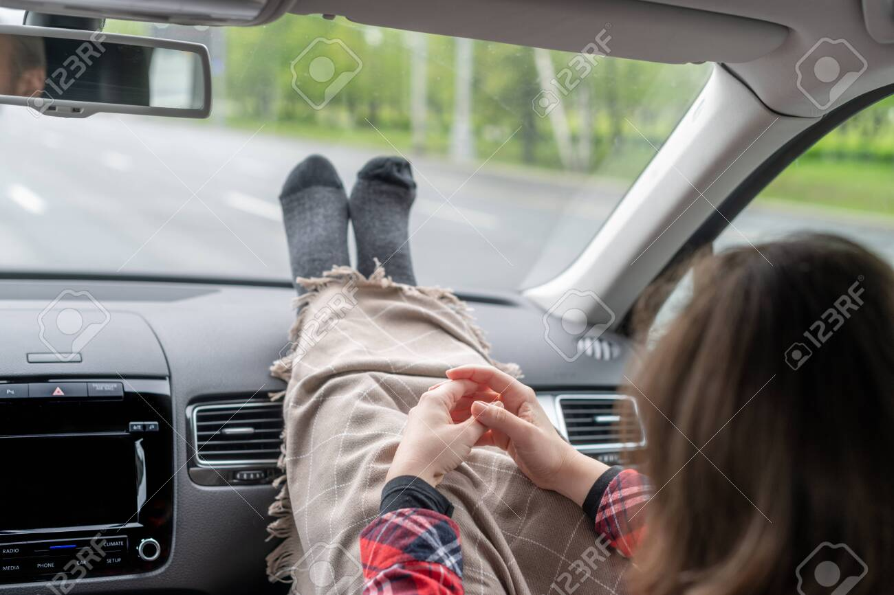Woman passenger legs in socks wrapped in a plaid on car dashboard while travel on the highway. Freedom concept. - 147673177