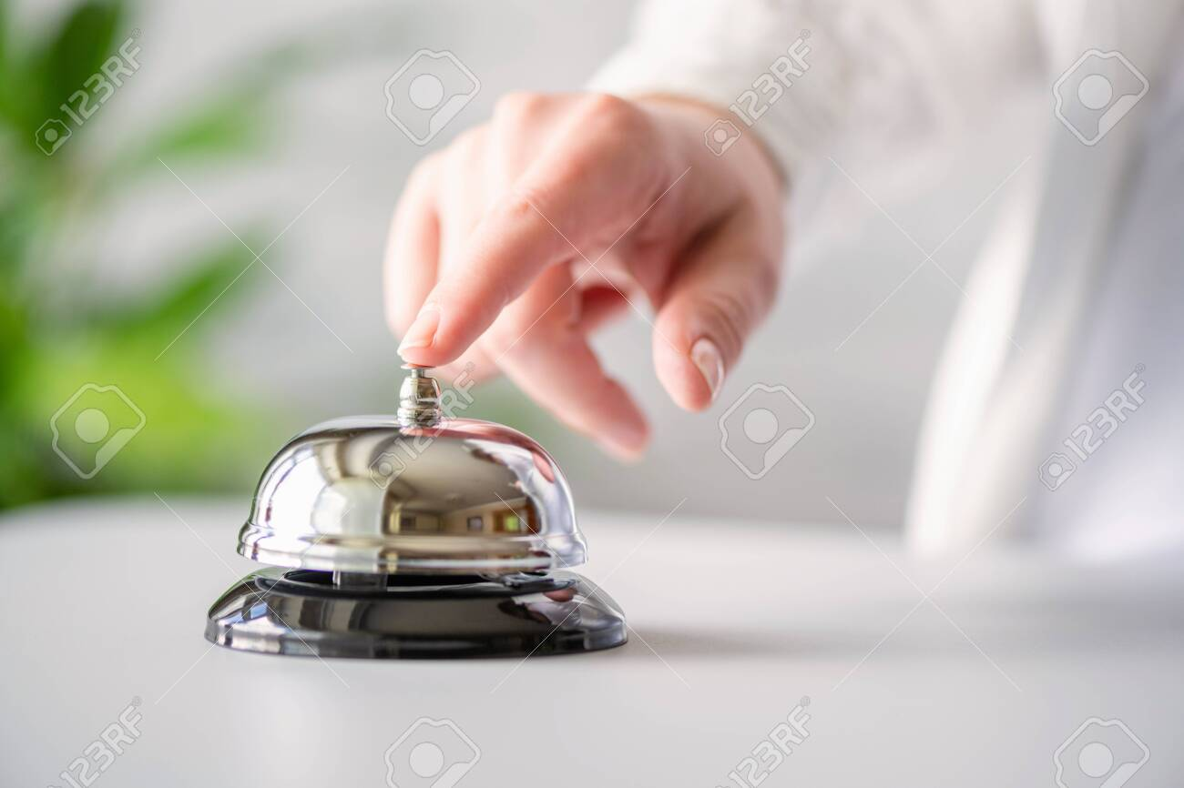 Hand of guest ringing in silver bell. reception desk with copy space. Hotel service. Selective focus - 147845323